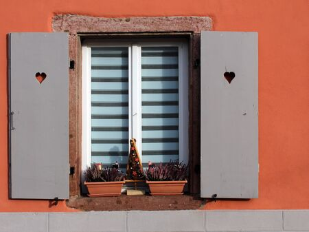 Shutter window with open wooden boards and flower pots on the window sill