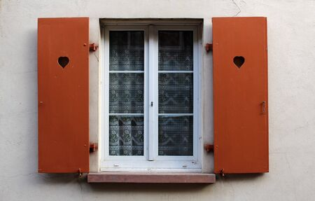 Shutter window with brown doors open on a rural house facade wall