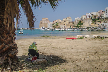 castellammare del golfo: woman who paints a landscape on the shore in Sicily