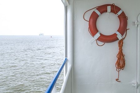 to drown: cuerda de color naranja con la boya de rescate en el mar barco n el fondo