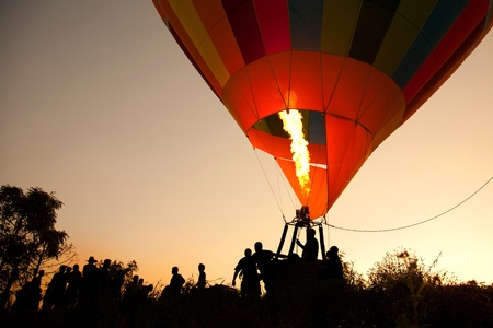 Silhouette hot air balloon adventure landing with many people
