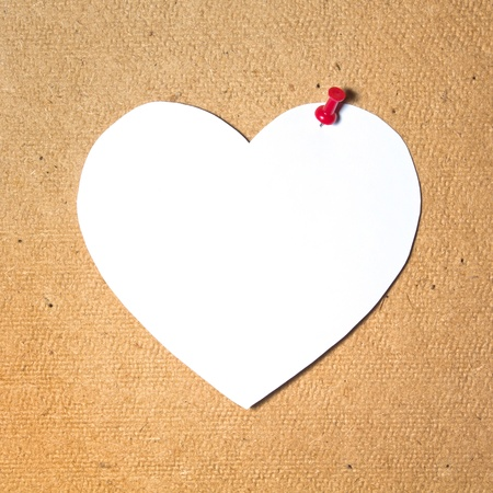 Note paper heart and red pins on cork board background photo