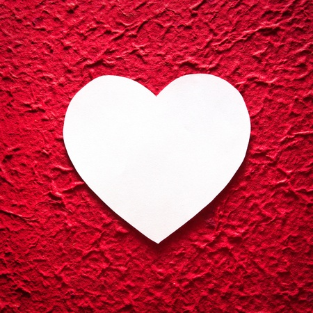 white heart-shaped paper on red background photo