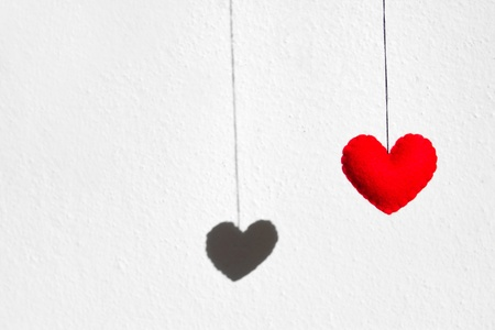 Red heart hanging together with the shadow on white concrete wall background