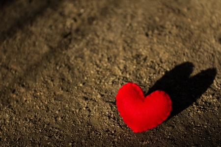 red evening: heart lying alone on the ground with her shadow