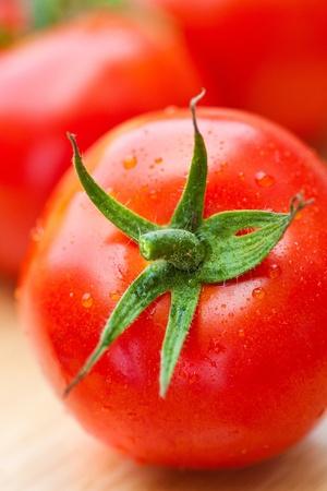Tomate rouge avec des gouttelettes d'eau sur la surface