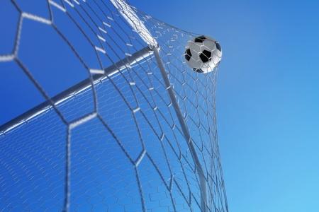 Ballon de soccer dans le filet sur l'objectif fond de ciel bleu