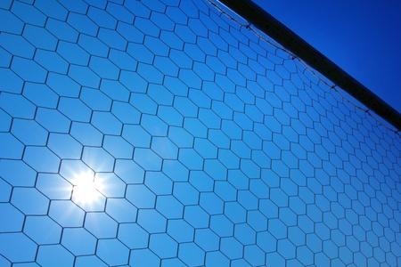 soccer net: Soccer net with sun on blue sky background