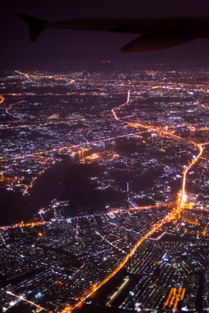 Night flight, airplane wing and night city view photo