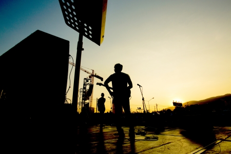 Silhouette of band preparing on a stage with sunset Stock Photo