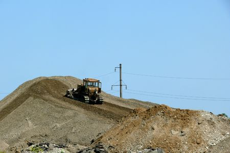 Work of the tractor on the hill of sand.