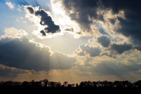 Sun Rays Beam through Dark Ominous Clouds with Silver Lining photo
