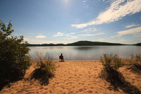 Sitting Alone on the Beach of a Calm Wilderness Lake photo