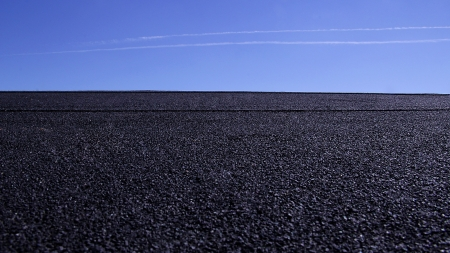 An empty parking lot or blacktop during the day with a jet in the sky Stock Photo