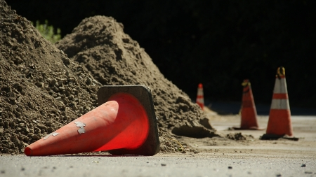 knocked over: Four traffic cones by two large piles of dirt on the side of the road  The first cone is knocked over