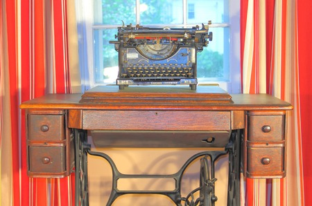 A vintage typewriter on a desk with red curtains