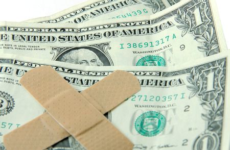 Dollar bills with band-aids = economic hardship photo