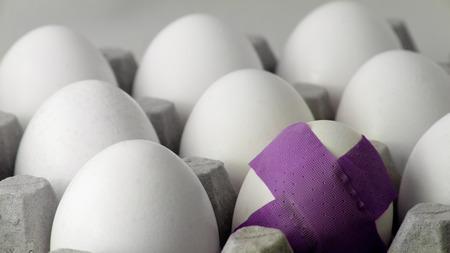 One egg has a purple bandage  Banque d'images