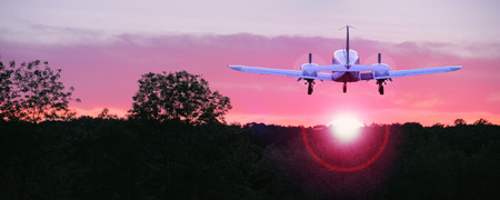 An airplane flying into the sunset, the ultimate symbol of freedom Stock Photo