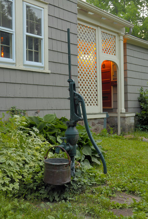 An outdoor water pump by the side of a nice home photo