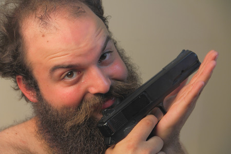 A balding bearded man mugs for the camera while displaying his pistol