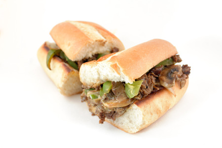 sandwich: Messy philly cheese steak with mushrooms, onions, and peppers Stock Photo