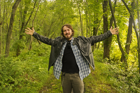 slicker: An excited city slicker spreads arms while wandering along a trail in the woods