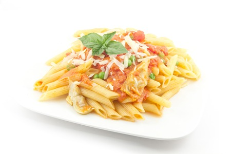 Delicious vodka penne garnished with basil leaves with artichoke hearts and green peas