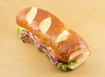 pretzel: A delicious roast beef pretzel roll sandwich ready to be eaten