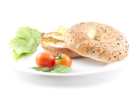 A yummy healthy breakfast bagel with eggs and fresh tomatoes photo