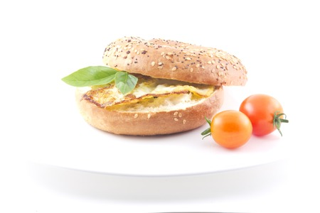 Yummy healthy breakfast bagel with basil garnish and cherry tomatoes photo