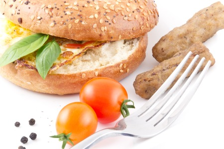 Yummy healthy breakfast bagel with sausage and cherry tomatoes