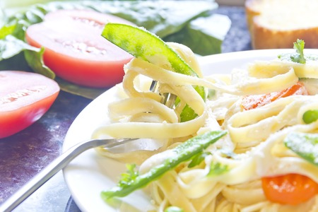 Fettuccini Alfredo with snap peas and carrots photo