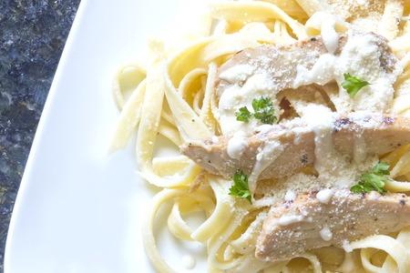 Chicken Fettuccini alfredo with fresh curly parsley photo