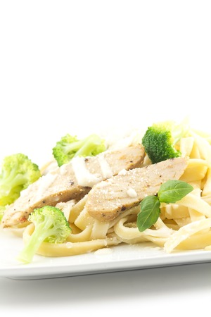 Chicken Fettuccini alfredo with fresh basil leaves and steamed fresh broccoli, delicious photo