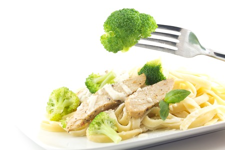 Chicken Fettuccini alfredo with fresh basil leaves and steamed fresh broccoli, delicious Imagens