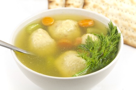Delicious Matzoh ball soup with crackers wine and dill photo