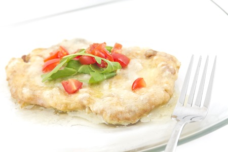 Veal schnitzel with savory lemon butter sauce. Arugula and diced tomatoes to top