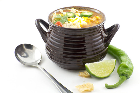 Hearty and spicy tortilla soup with hot peppers and cilantro garnish photo