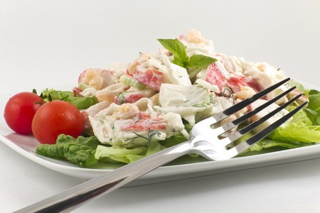 Mayonnaise seafood salad with shrimp and crab meat and fresh dill, romaine lettuce, and basil leaf garnish