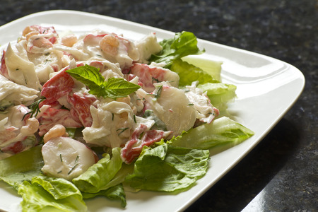 Mayonnaise seafood salad with shrimp and crab meat and fresh dill, romaine lettuce, and basil leaf garnish photo