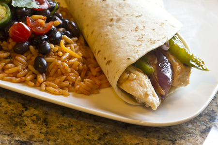 Mexican chicken fajita with green bell pepper slices and red onion in a flour tortilla, with black beans and rice on the side photo