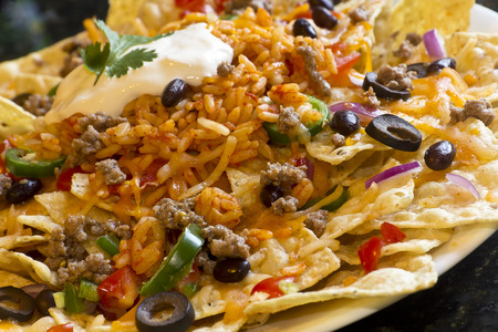 Mexican nachos with sour cream, black olives, ground beef, black beans, tomatoes, shredded cheese, jalapenos, rice, and cilantro