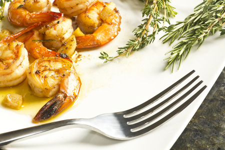 Authentic Portuguese Garlic Shrimp garnished with rosemary and thyme photo