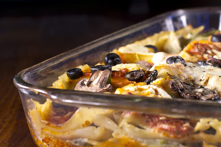 Homade vegetarian lasagna casserole topped with sliced mushrooms, olives, and artichoke hearts