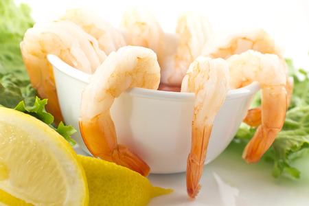 tiger shrimp: fresh shrimp cocktail with sauce, lemon wedges, and garnished with crispy romaine lettuce