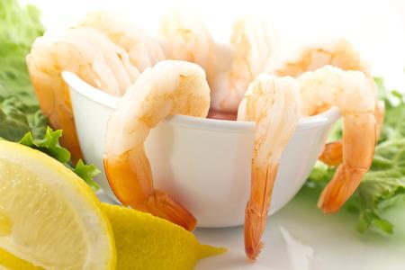 shrimp cocktail: fresh shrimp cocktail with sauce, lemon wedges, and garnished with crispy romaine lettuce
