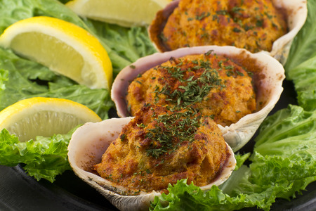 seasoned: Stuffed seasoned clams garnished with romaine lettuce and lemon wedges on a rustic platter