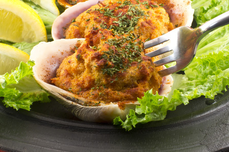 Stuffed seasoned clams garnished with romaine lettuce and lemon wedges on a rustic platter