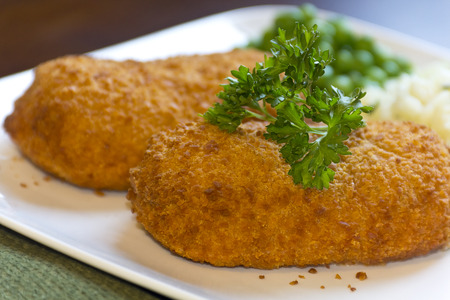 bleu: Breaded stuffed chicken cordon bleu with green peas white rice and parsley for garnish